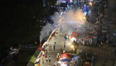 People walk by the street market during Loi Krathong celebration in Tak. Stock Footage