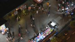 People walk by the street market during Loi Krathong celebration. - stock footage