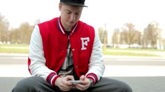 Man in fullcap and sportsuit sitting near the street and writing text messages Stock Footage