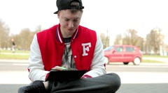 Student in fullcap and sportsuit sitting on a wall and writing into notebook Stock Footage