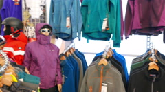 Tourist  outdoor clothes on angers. Panorama in  outdoor shop, blurred scene. Stock Footage