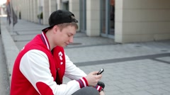 Student in fullcap and sportsuit sitting near the street and writing sms Stock Footage
