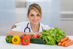 Portrait Of Female Dietician With Vegetables On Desk - stock photo