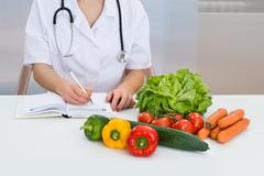 Close-up Of Female Dietician Writing Prescription With Vegetables On Desk - stock photo