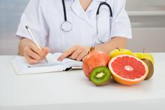 Close-up Of Female Dietician Writing Prescription With Fruits On Desk - stock photo