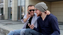 Two, handsome boys sitting near building and using cellphones (51) Stock Footage