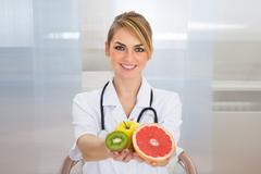 Portrait Of Happy Female Dietician Holding Fruits - stock photo