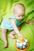 Adorable little baby playing with educational toys - stock photo