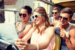 group of smiling friends traveling by tour bus - stock photo