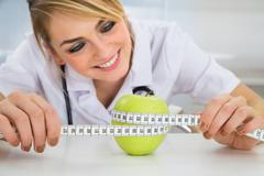 Happy Female Dietician Measuring Green Apple With Measuring Tape - stock photo