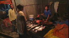 Indian boy cutting fish while talking to a man and woman. Stock Footage