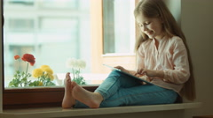 Shows ok. Thumbs up. Closeup blond little girl using tablet pc and sitting on Stock Footage