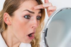 Close-up Of Shocked Woman Looking At Pimple In Mirror Stock Photos