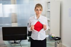 Portrait Of Young Businesswoman Tearing Her Shirt Revealing A Superhero Suit Stock Photos