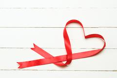 White background with heart shaped ribbon - stock photo