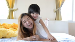 Happy family. Asian mother and son playing and smiling on bed Stock Footage