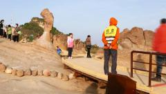 Timelapse: tourists posing with Queen's Head Rock at Yehliu Geopark Stock Footage