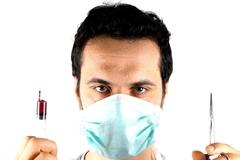 Studio shot of a young man with surgical mask - stock photo
