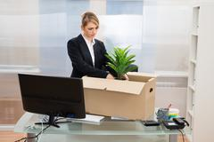 Stock Photo of Unhappy Businesswoman Packing Her Belongings In Box