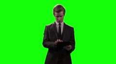 Young businessman using mobile device / tablet computer against green screen Stock Footage