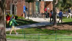 College Students Walking Around Busy Campus on Cool Spring Day - stock footage