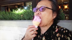 Happy old woman eating strawberry ice cream at park Stock Footage