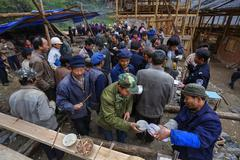 Rural festivities, villagers drink alcohol and take their food together. - stock photo