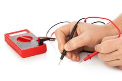 Hands and electric multimeter Stock Photos