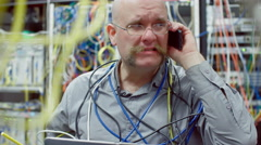 Technical support guy hangs up phone in cluttered server room 4K Stock Footage