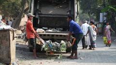 Indian men throwing garbage in the truck at street in Mumbai. Stock Footage