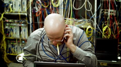 IT worker examines a component in a cluttered server room 4K Stock Footage