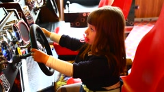 Little girl playing and drive with the wheel of a game console Stock Footage
