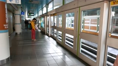 Taipei Rapid Transit train arrival at overground station glass doors and wall Stock Footage