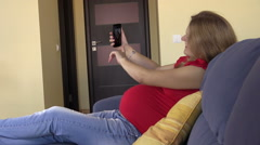 Happy pregnant woman shoot selfie with smartphone, browse photo Stock Footage