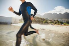Triathletes rushing into the water Stock Photos