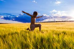 jumping boy on the wheat field - stock photo