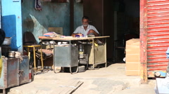 Indian man working behind a table at the storage room entrance. - stock footage