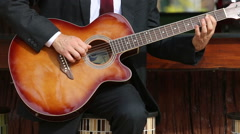 Bearded musician in suit and white shirt plays guitar sitting at bar board Stock Footage