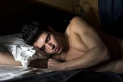 Handsome shirtless athletic young man sleeping  in bed - stock photo