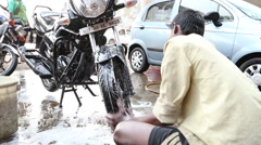 Indian man cleaning motorbike at a street in Mumbai. Stock Footage