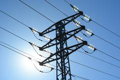 Electric high voltage tower against the sun Stock Photos