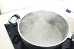Boiling water in pot in kitchen, slow motion shot at 240fps NTSC Stock Footage