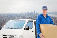Composite image of happy delivery man holding cardboard box - stock photo
