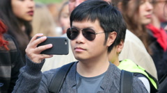 Asian man filming with phone in public Stock Footage