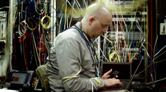 Tech support guy working on laptop in a cluttered server room 4K Stock Footage