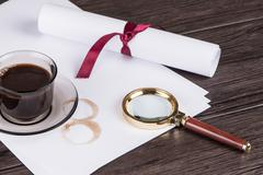Coffee cup, paper sheets and detective magnifying glass Stock Photos