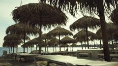 Tropical summer beach setting,bamboo umbrellas,deck chairs Stock Footage