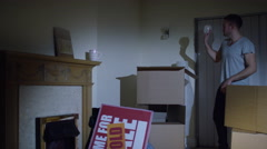 4K Happy young couple sitting amongst cardboard boxes in their new home Stock Footage