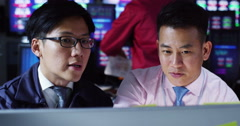 Stock Video Footage of 4K Asian financial brokers watching the world markets in a busy trading room