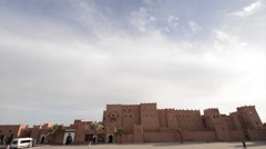 Stock Video Footage of People and cars passing by Kasbah Taourirt in Ouarzazate.